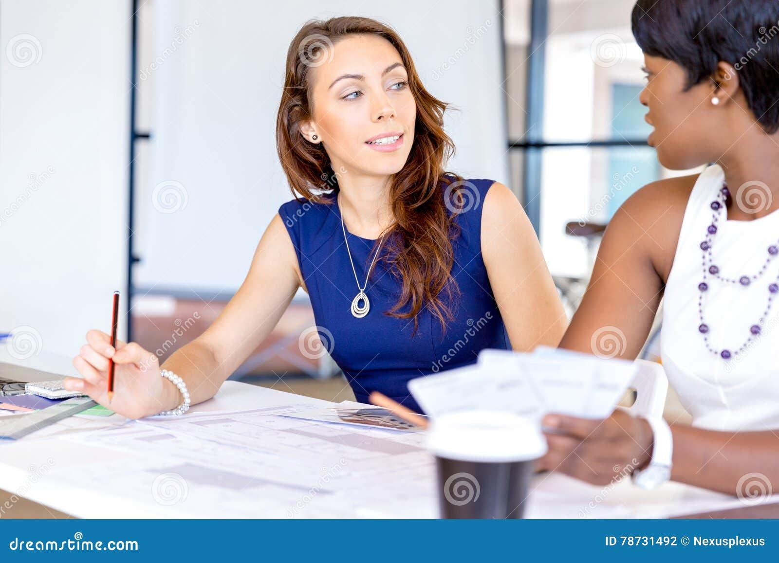 Unga kvinnor som sitter på ett skrivbord i ett kontor och ett arbete på ritning