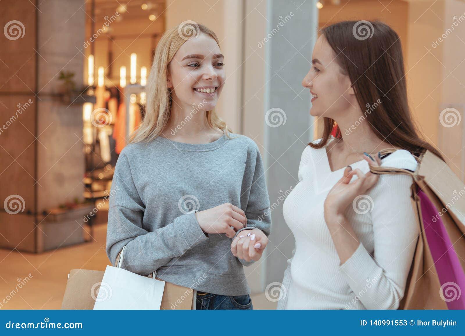 Unga kvinnor som tycker om att shoppa tillsammans på gallerian