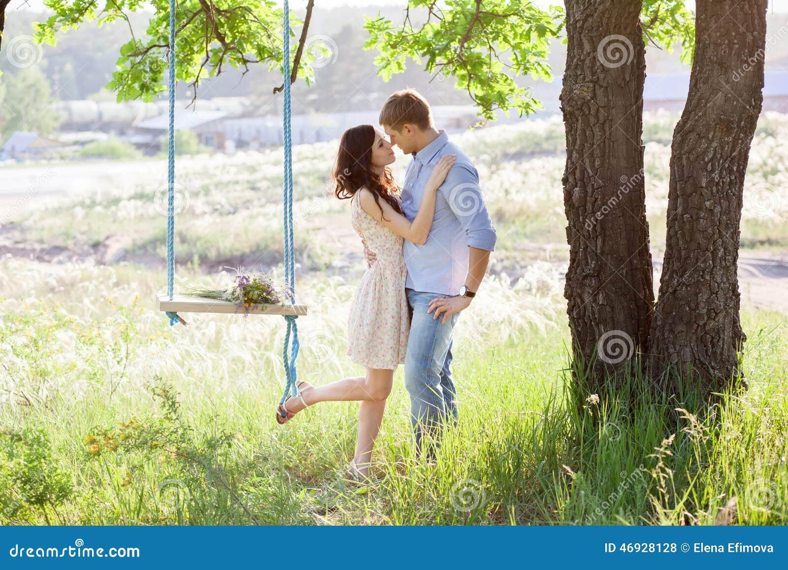 Unga kyssande par under stort träd med gunga