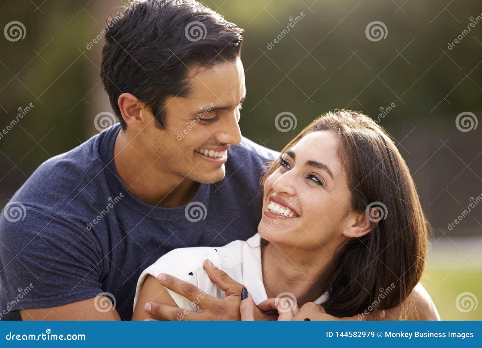Unga latinamerikanska par som ser de som ler, slut upp