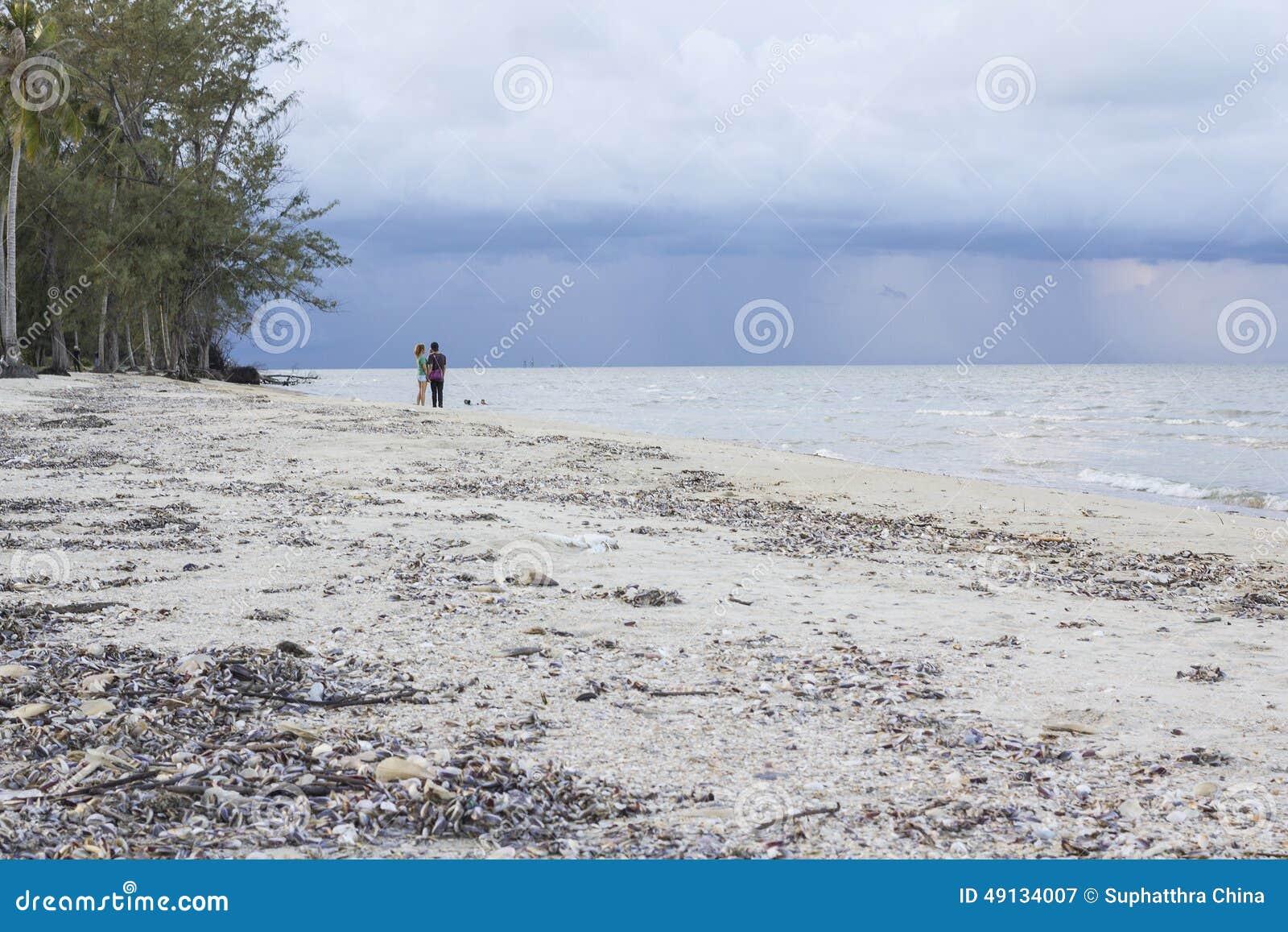 Unga lyckliga asiatiska thailändska par på den tropiska stranden