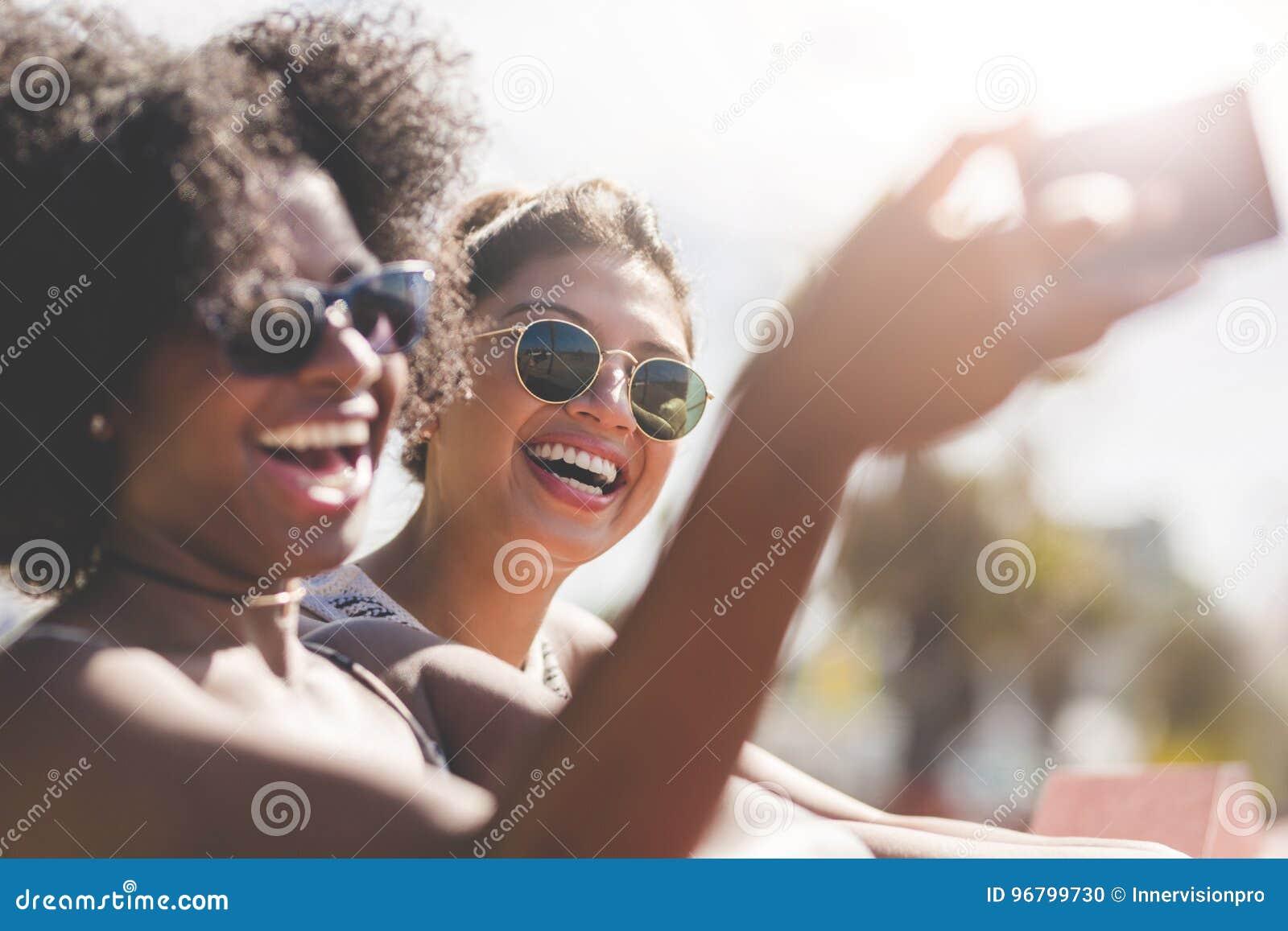 Unga lyckliga kvinnor som tar sig fotoet vid mobilen