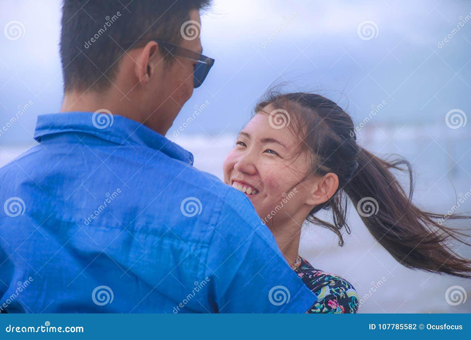 Unga lyckliga och härliga kinesiska asiatiska par med kvinnan kramar hennes pojkvänromantiker och kelar på stranden