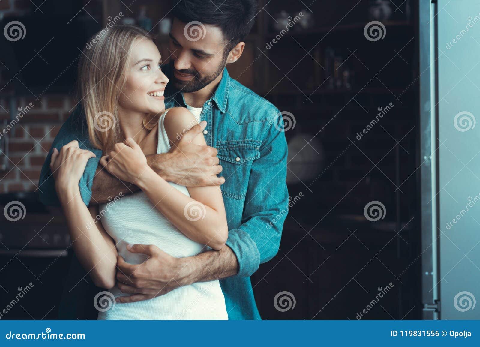 Unga lyckliga par som kramar och ser de i inre av ett nytt kök, lycka i ett nytt hem