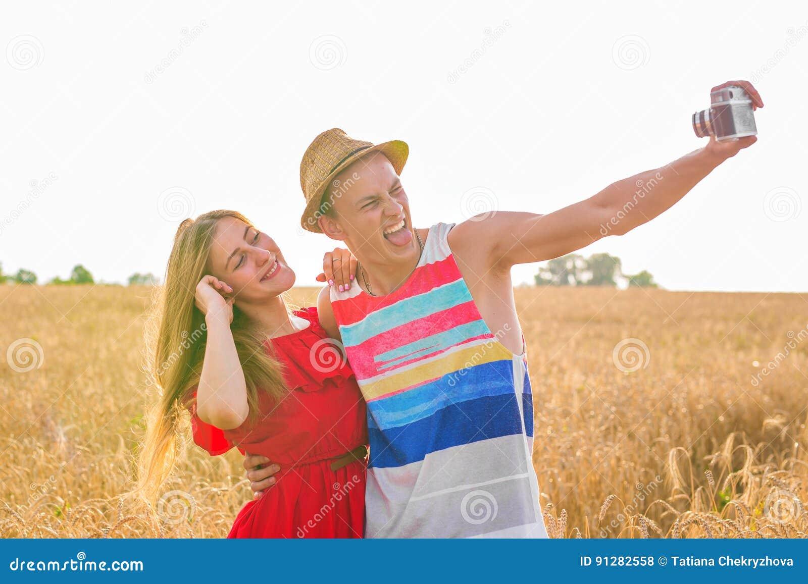Unga lyckliga par som tar en selfie i fältet