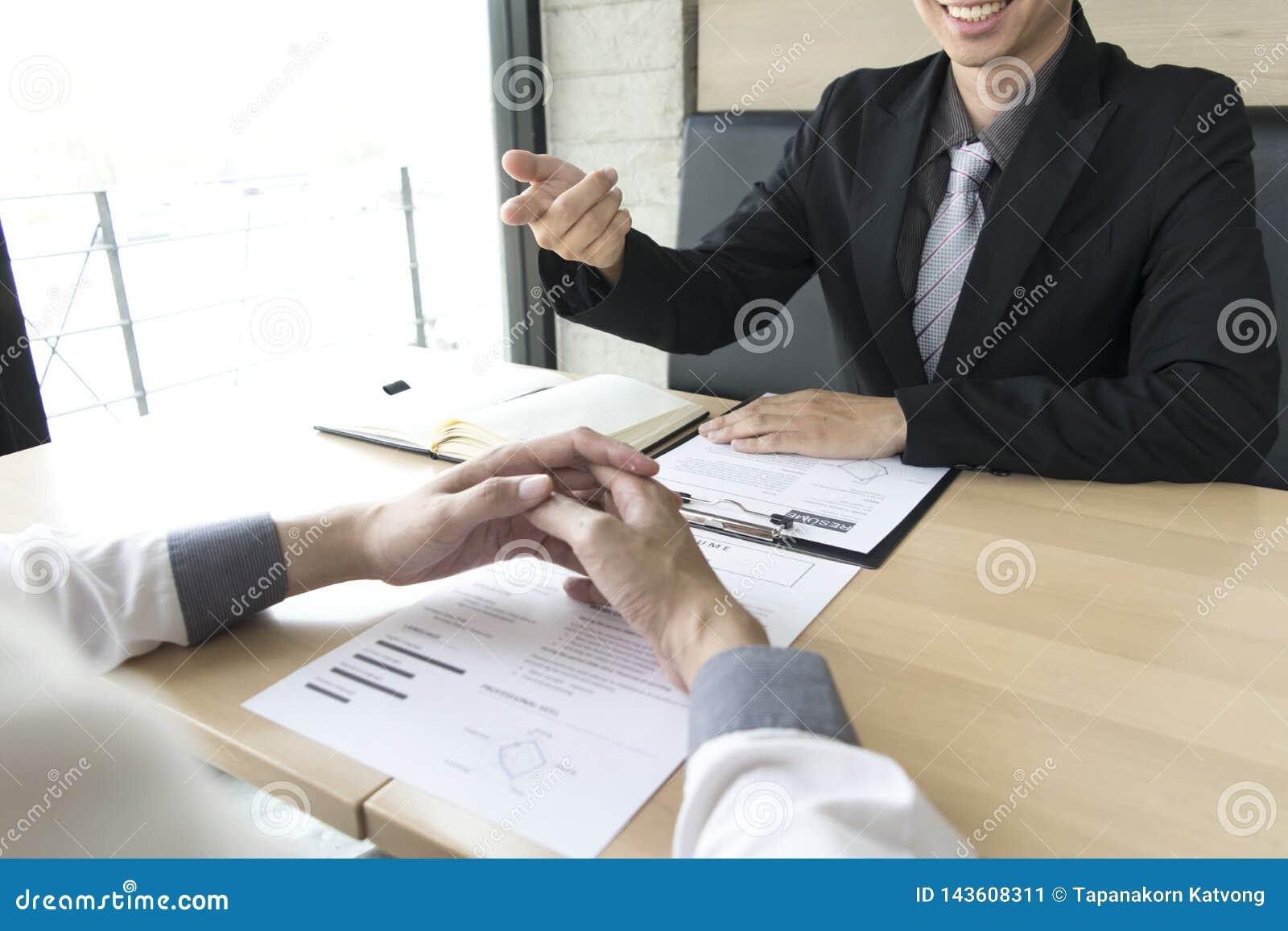 Unga män intervjuas av arbetsgivare Arbetsgivaren bär en svart dräkt som förklarar platsansökan