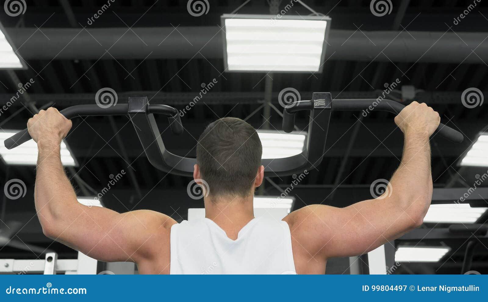 Unga muskulösa mandrev på idrottshallen Idrottsman nen av viktutbildning