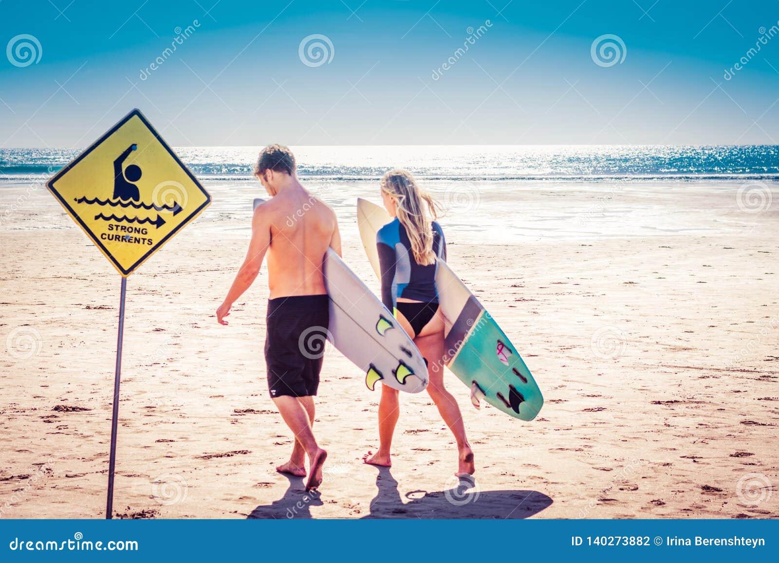 Unga par av surfare som går med där surfingbrädor i väg från fotografen in mot havet förbi starka strömmar