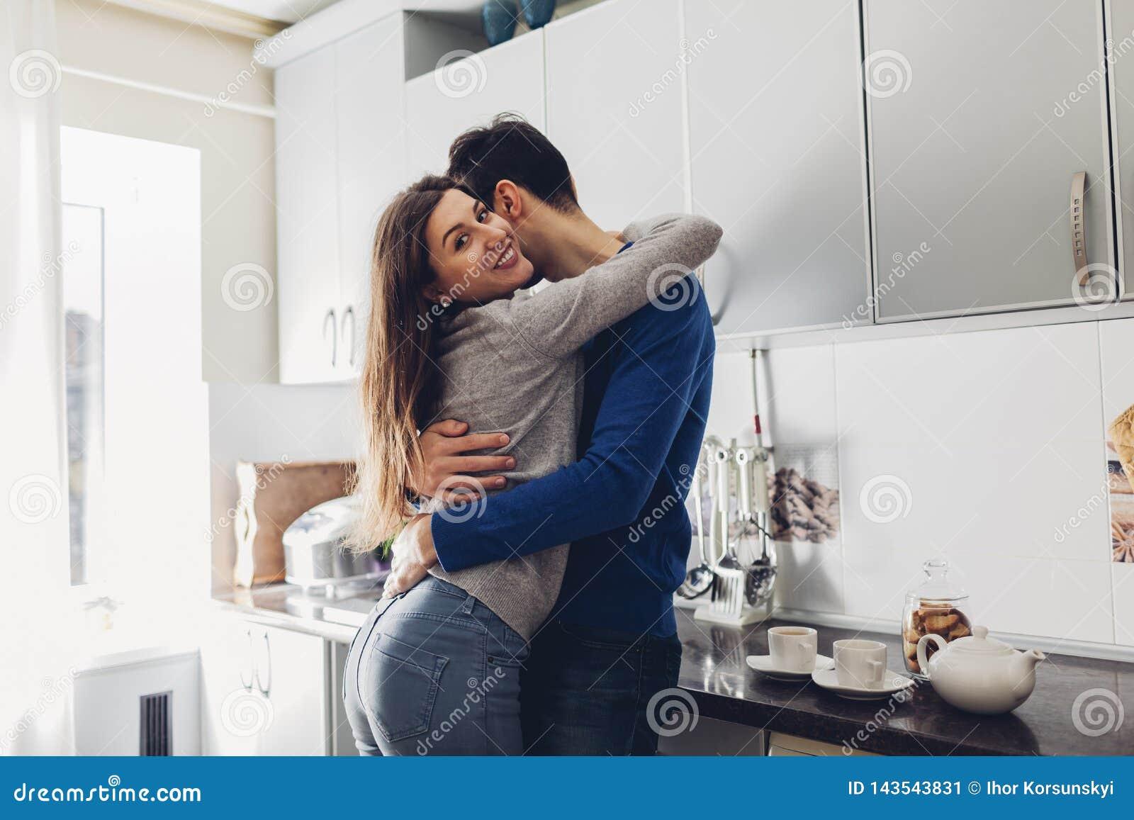 Unga par i köket som kramar och gör te