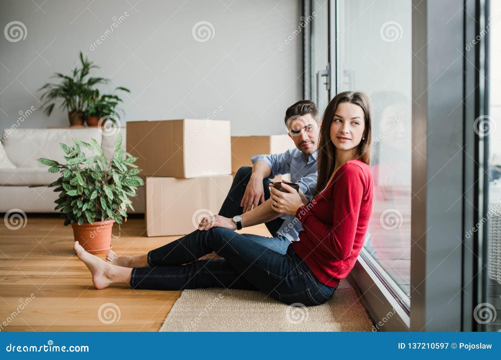 Unga par med kartonginflyttning ett nytt hem som sitter på ett golv