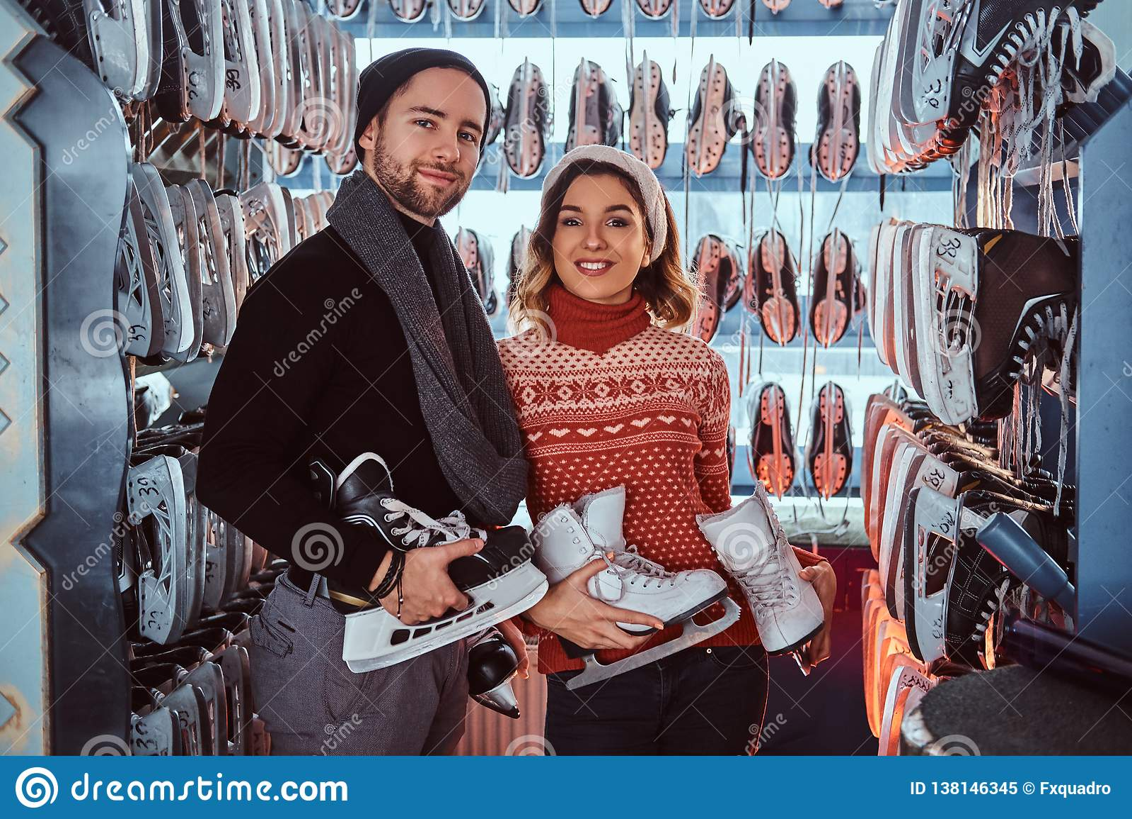 Unga par som bär varm kläder som står nära kuggen med många par av skridskor som väljer hans format