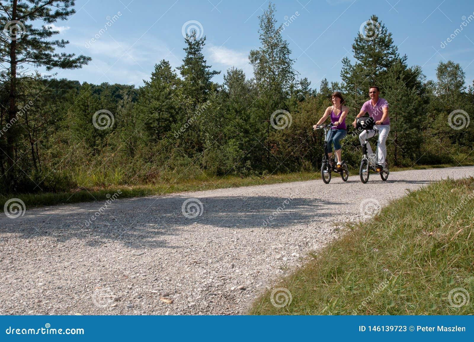 Unga par som cyklar med moderna små e-cyklar