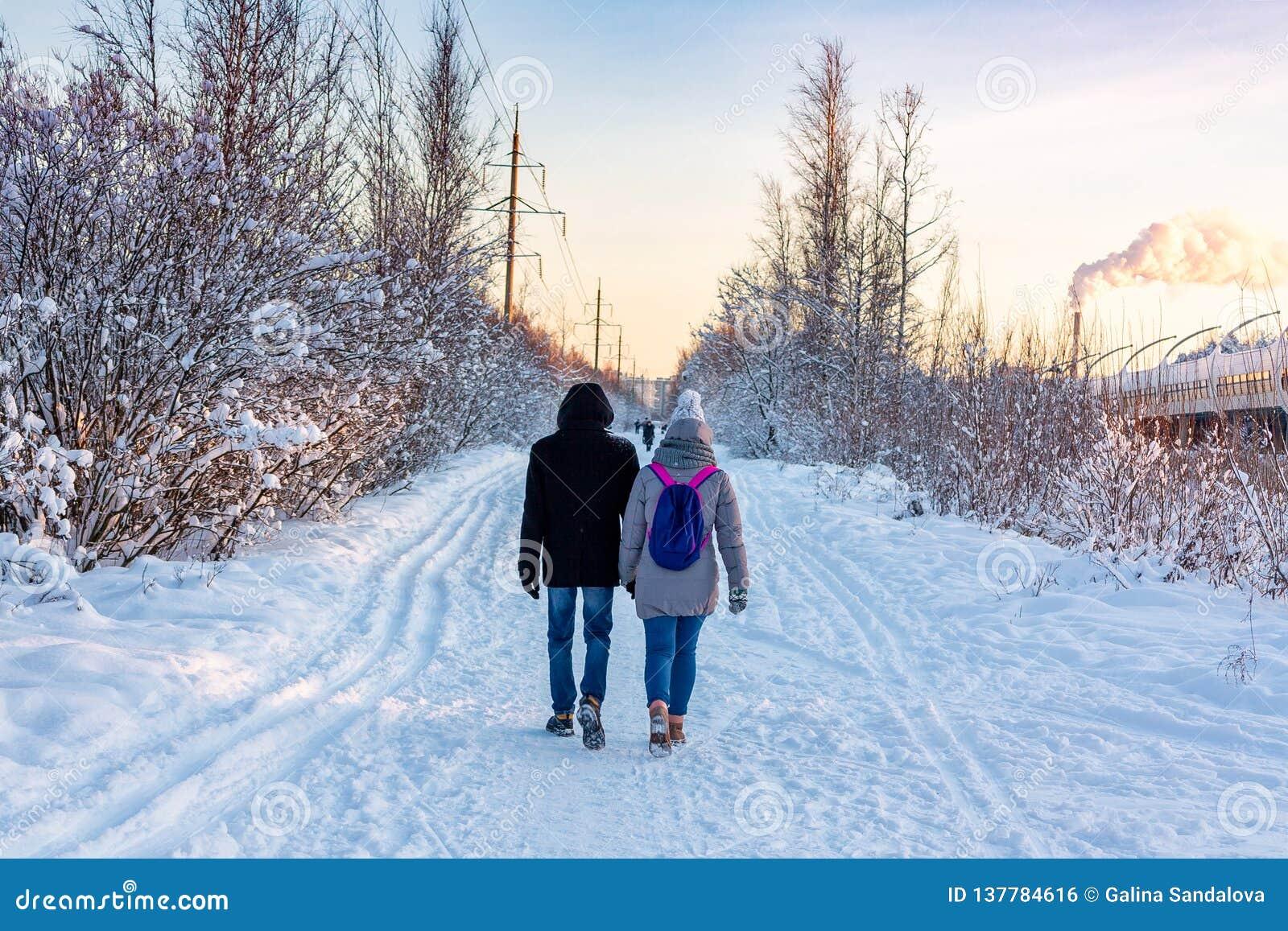 Unga par som går i, parkerar i en solig frostig dag för vinter