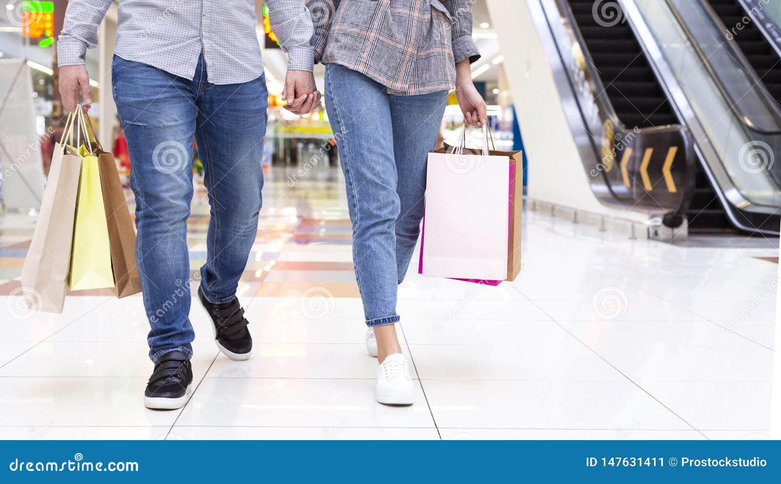 Unga par som går i shoppinggallerian, skörd