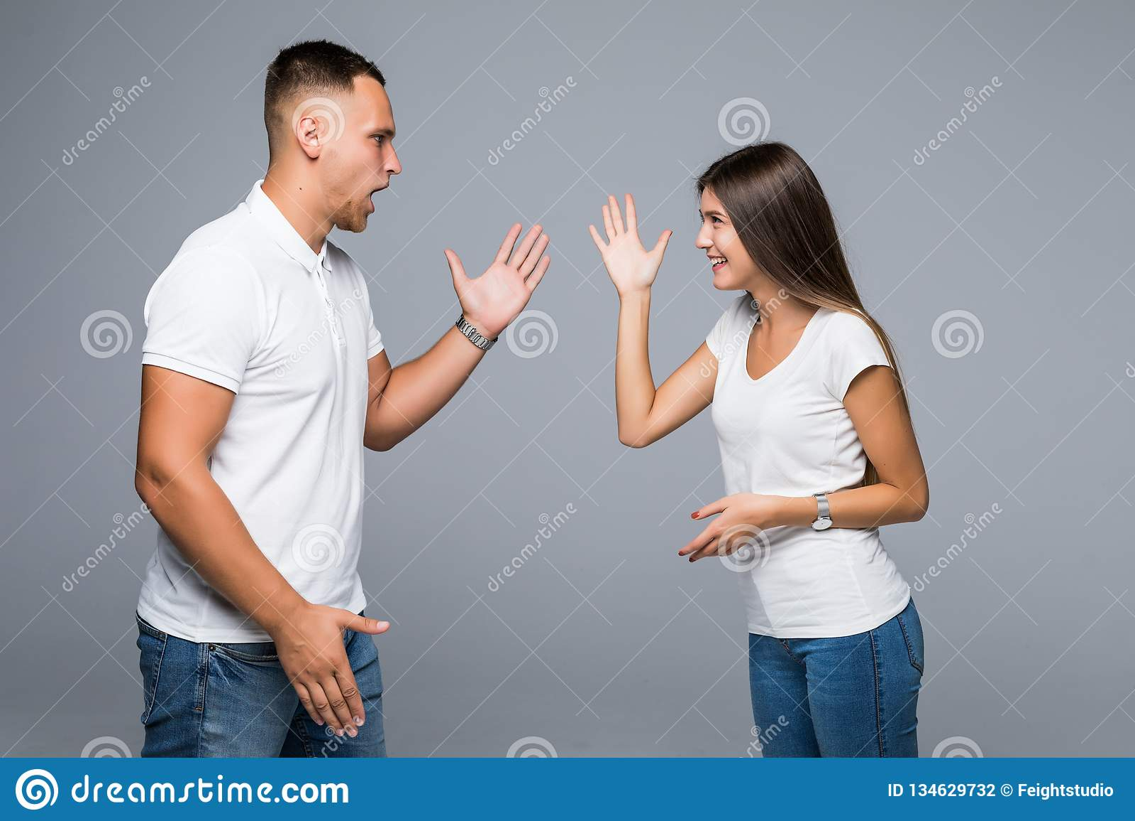 Unga par som har argument på grå bakgrund Barnpar som gr?lar och att ropa