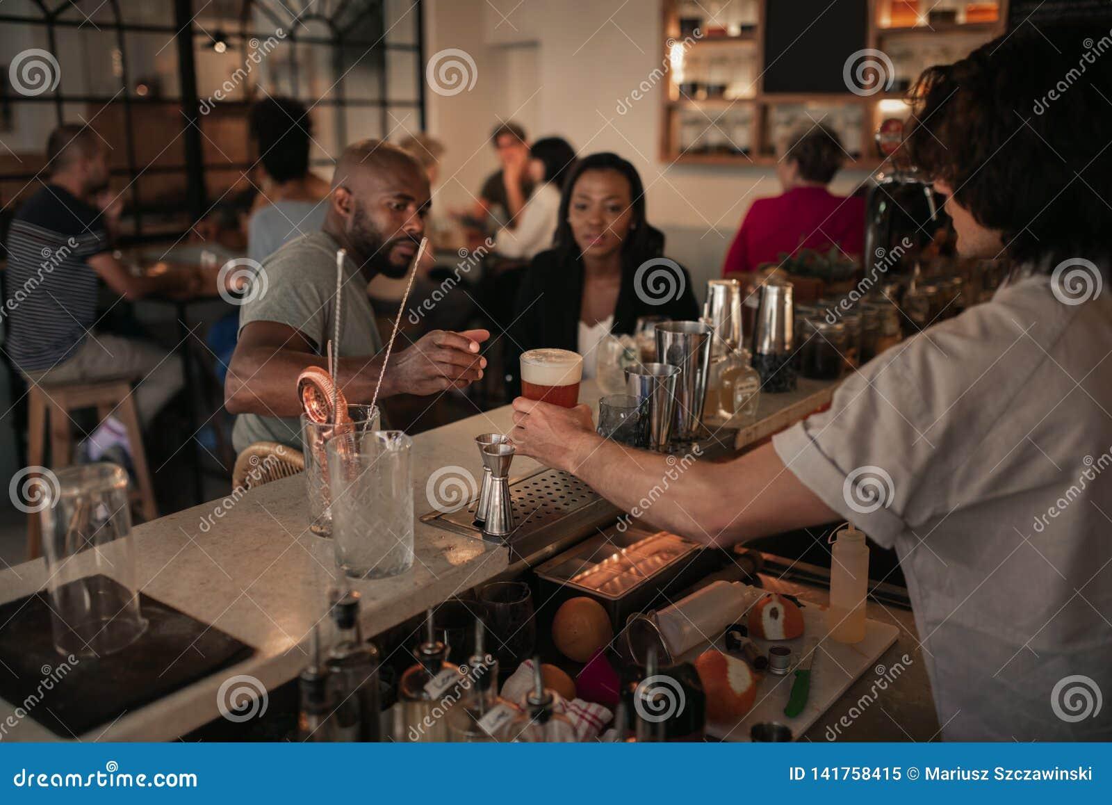 Unga par som har drinkar på en stång i aftonen