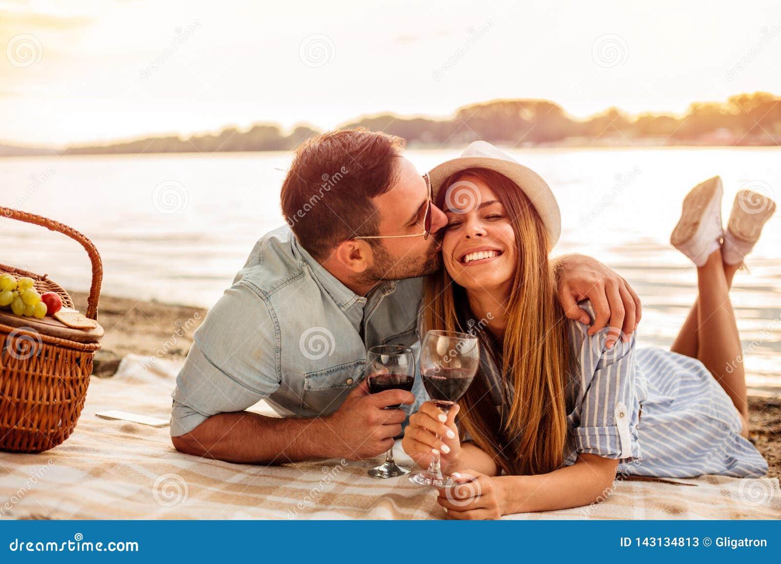 Unga par som har en picknick på stranden Mannen är krama och kyssa hans flickvän