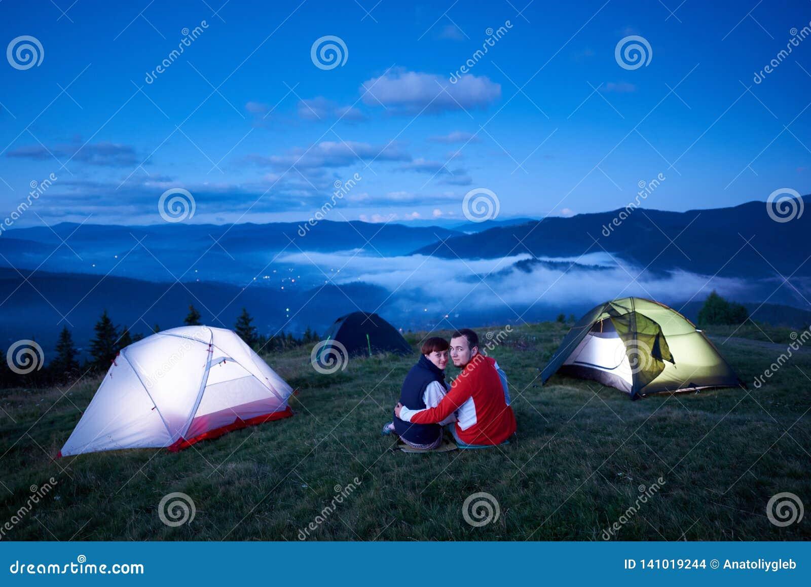 Unga par som sitter nära tältuniversitetsområde på bakgrund av berglandskapet