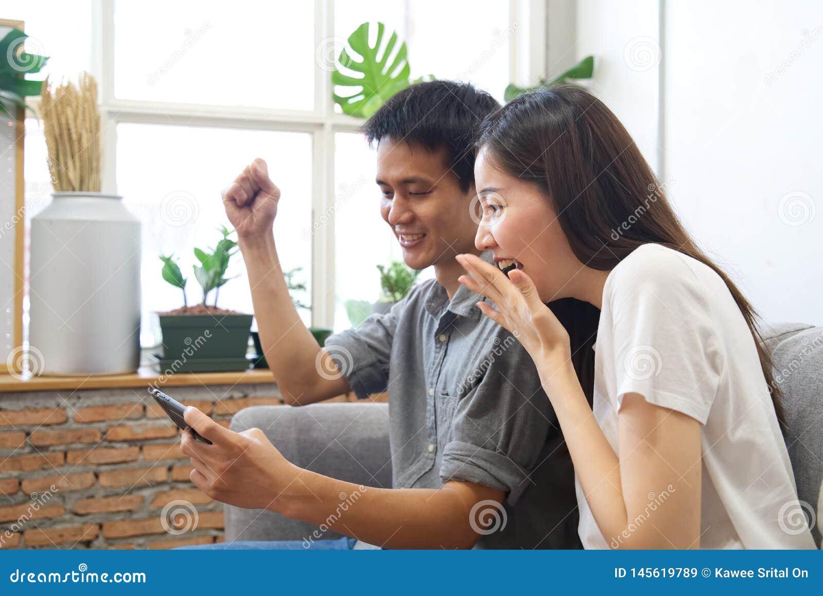 Unga par som sitter på soffan, håller ögonen på mobiltelefonen och känner sig surprise&happy