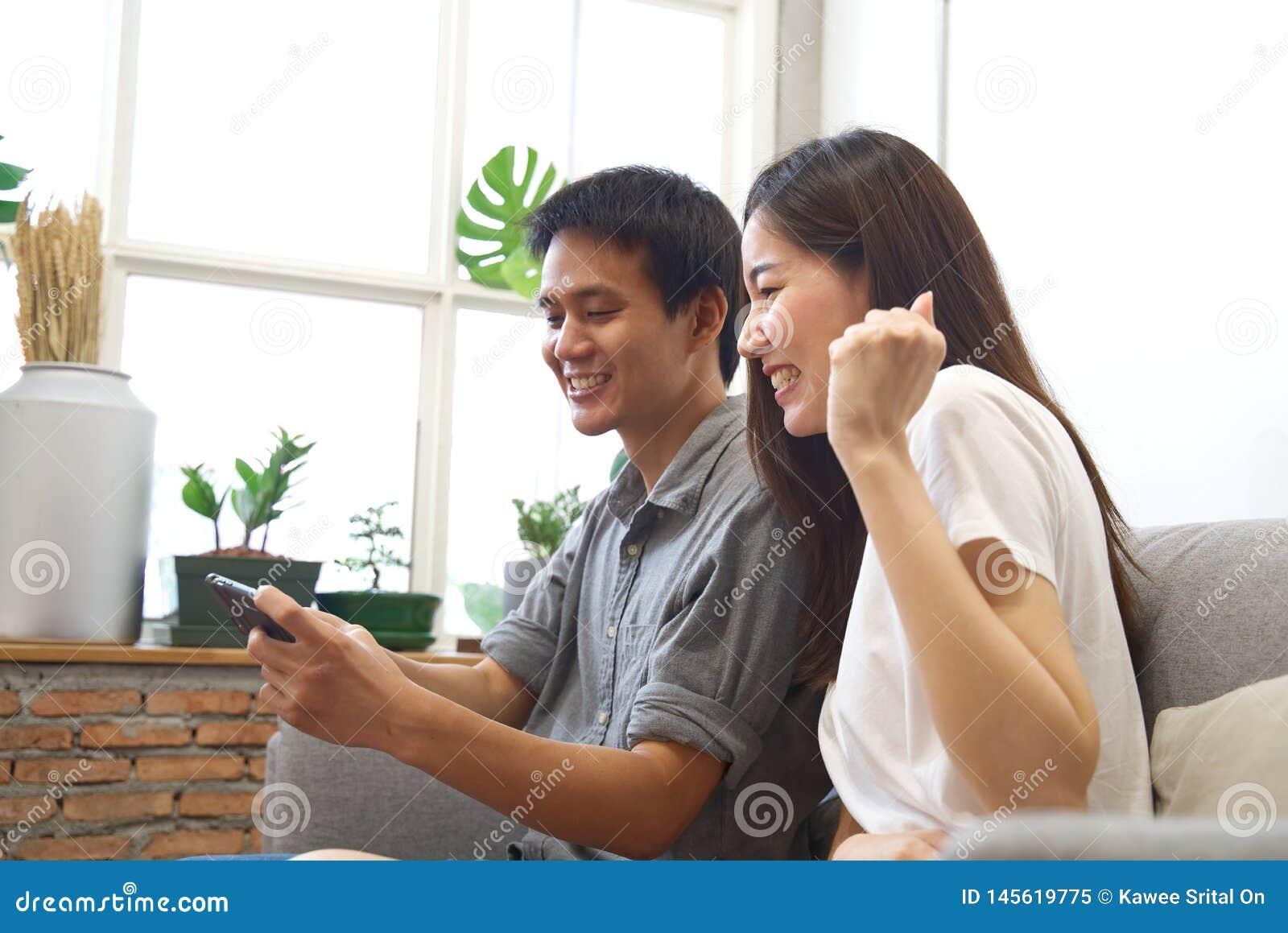 Unga par som sitter på soffan, håller ögonen på mobiltelefonen och känner sig surprise&happy, när vet resultatet med leendeframsi