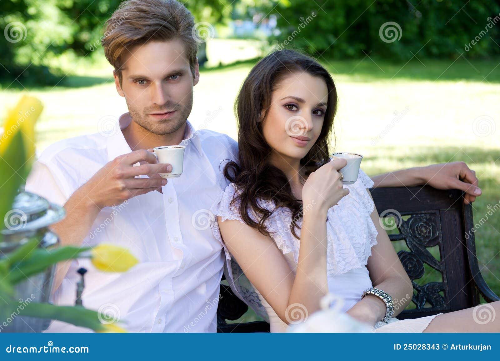 Unga par som tycker om lunch i trädgården