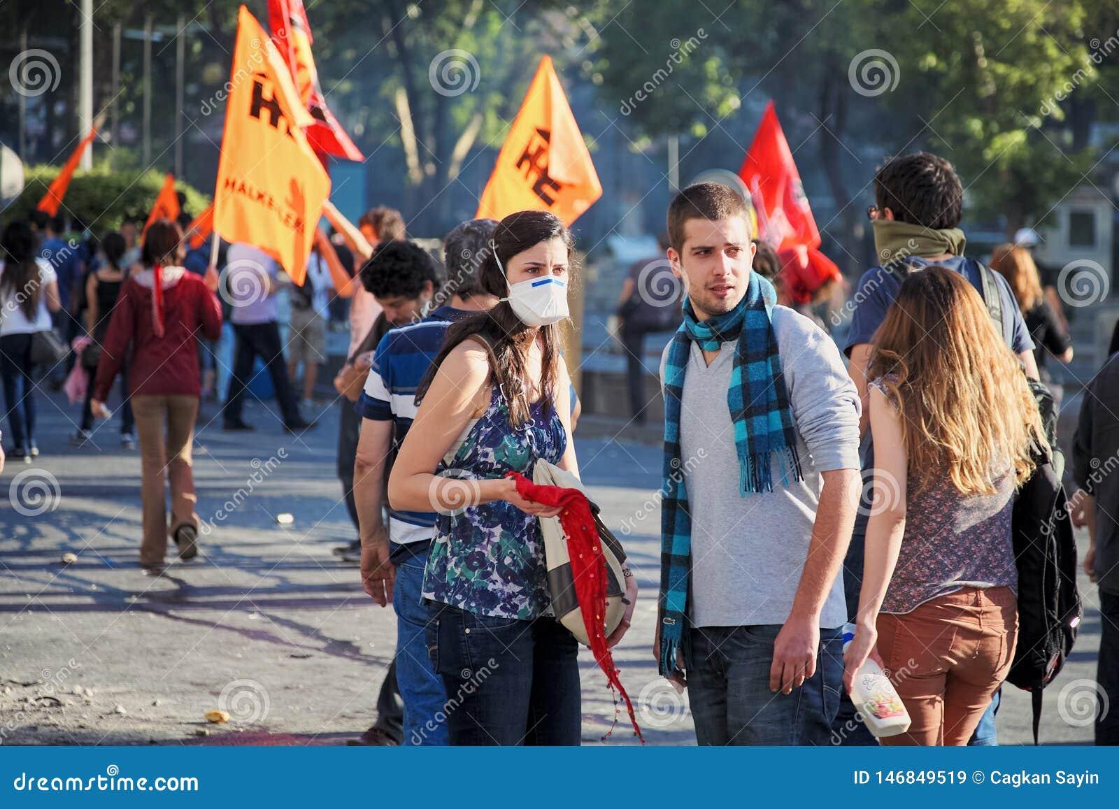 Unga person som protesterarpar i folkmassan som tillbaka ser under Gezi, parkerar angeläget protester i Ankara, den Kizilay fyrka