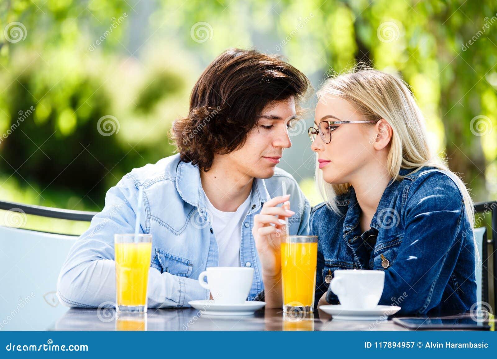 Unga romantiska par som tillsammans spenderar sammanträde för tid - i kafé` s
