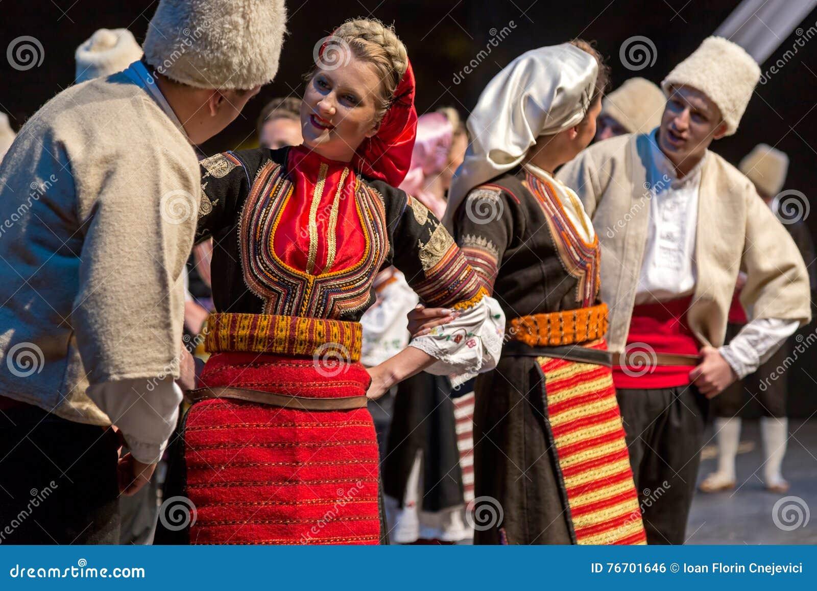 Unga serbiska dansare i traditionell dräkt