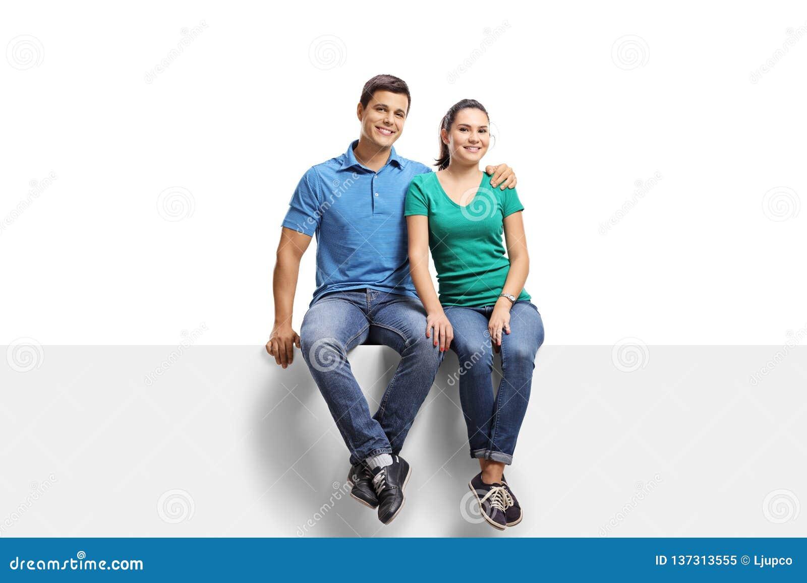 Unga tillfälliga par som sitter på en panel och ler på kameran