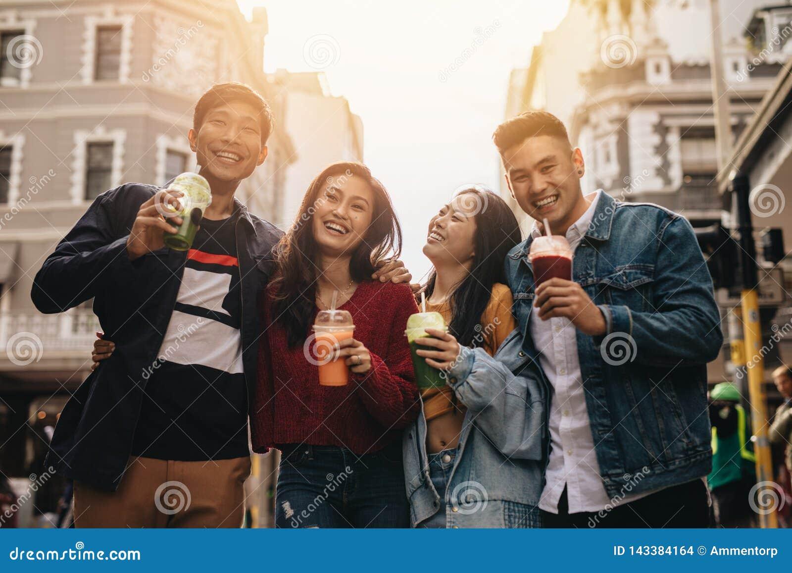 Unga vänner på stadsgatan med fruktsaft