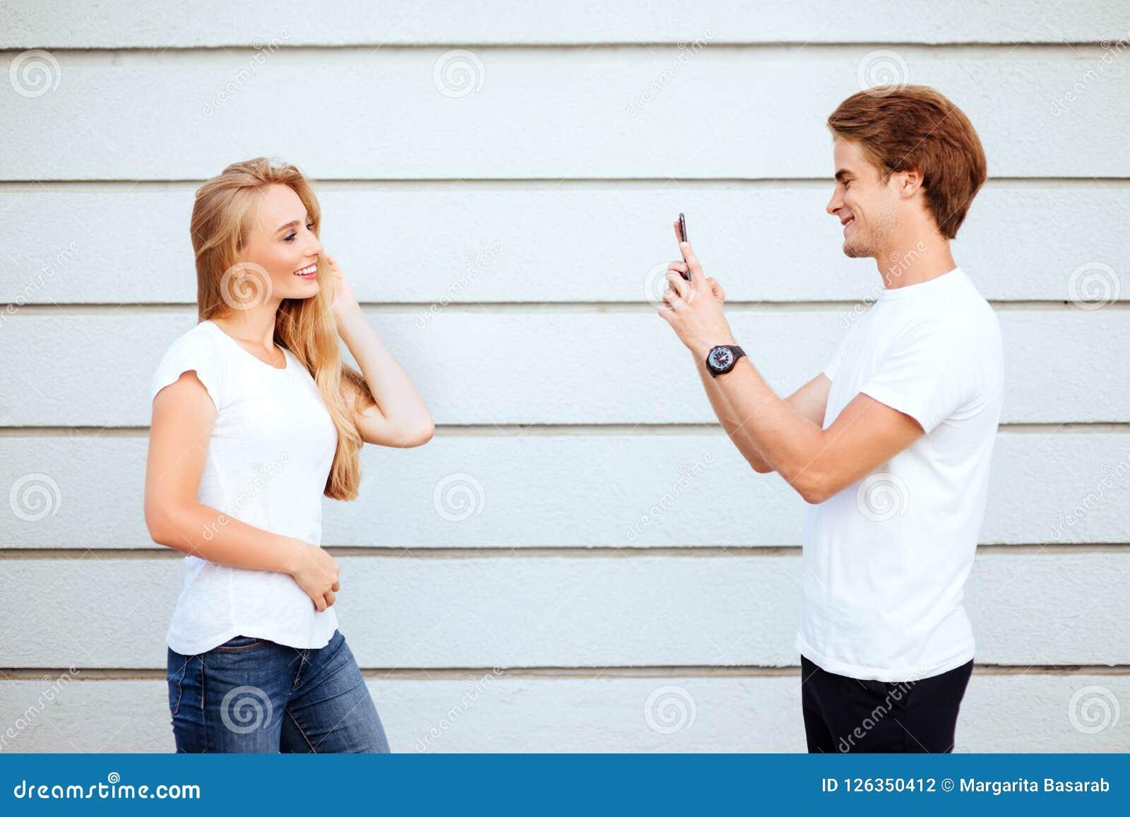 Unga vuxna hipsters pojken och flickan i vita T-tröja ler och danandeselfie