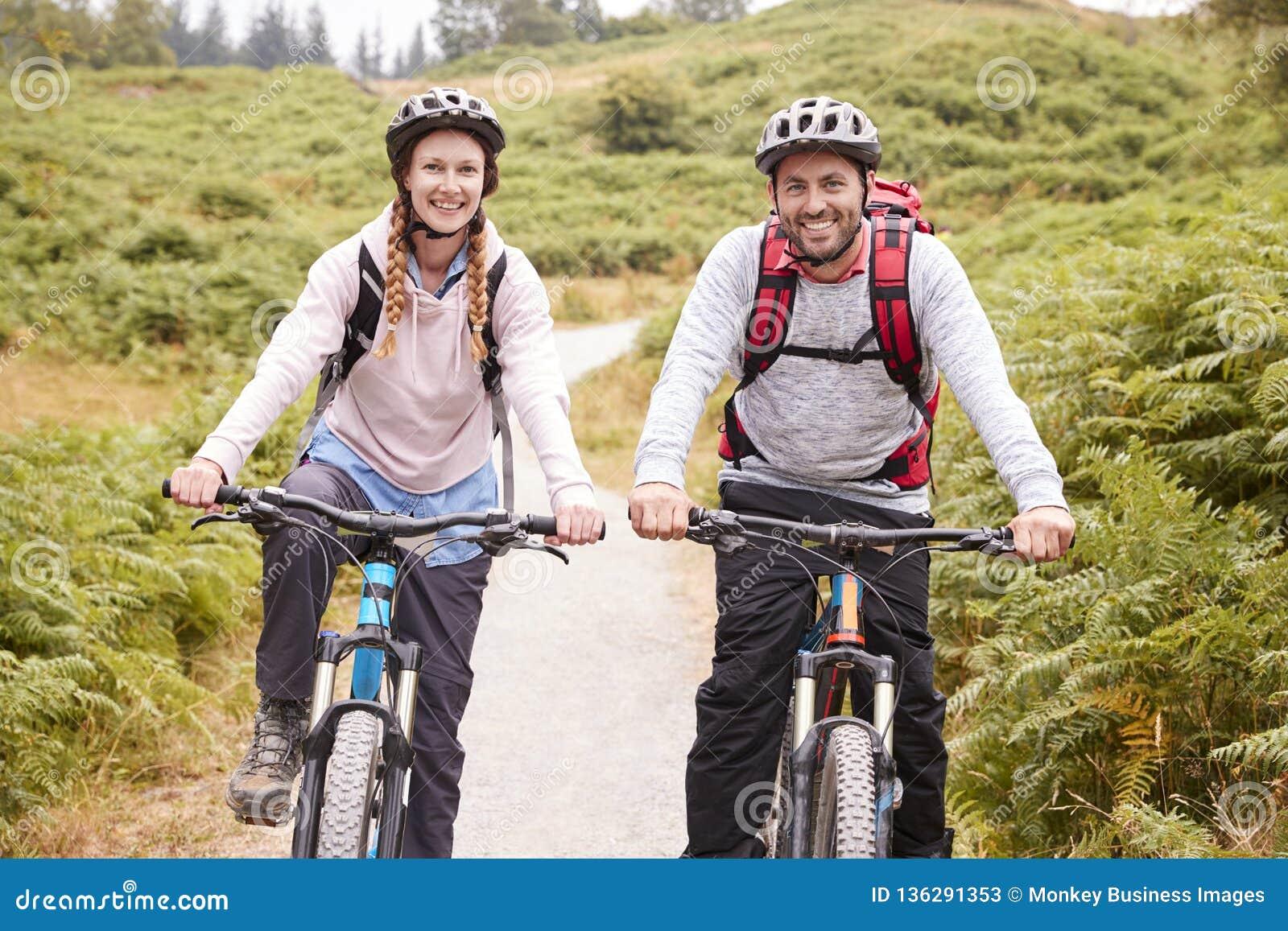 Unga vuxna par som rider mountainbiken i en landsgränd som ser upp kameran, slut