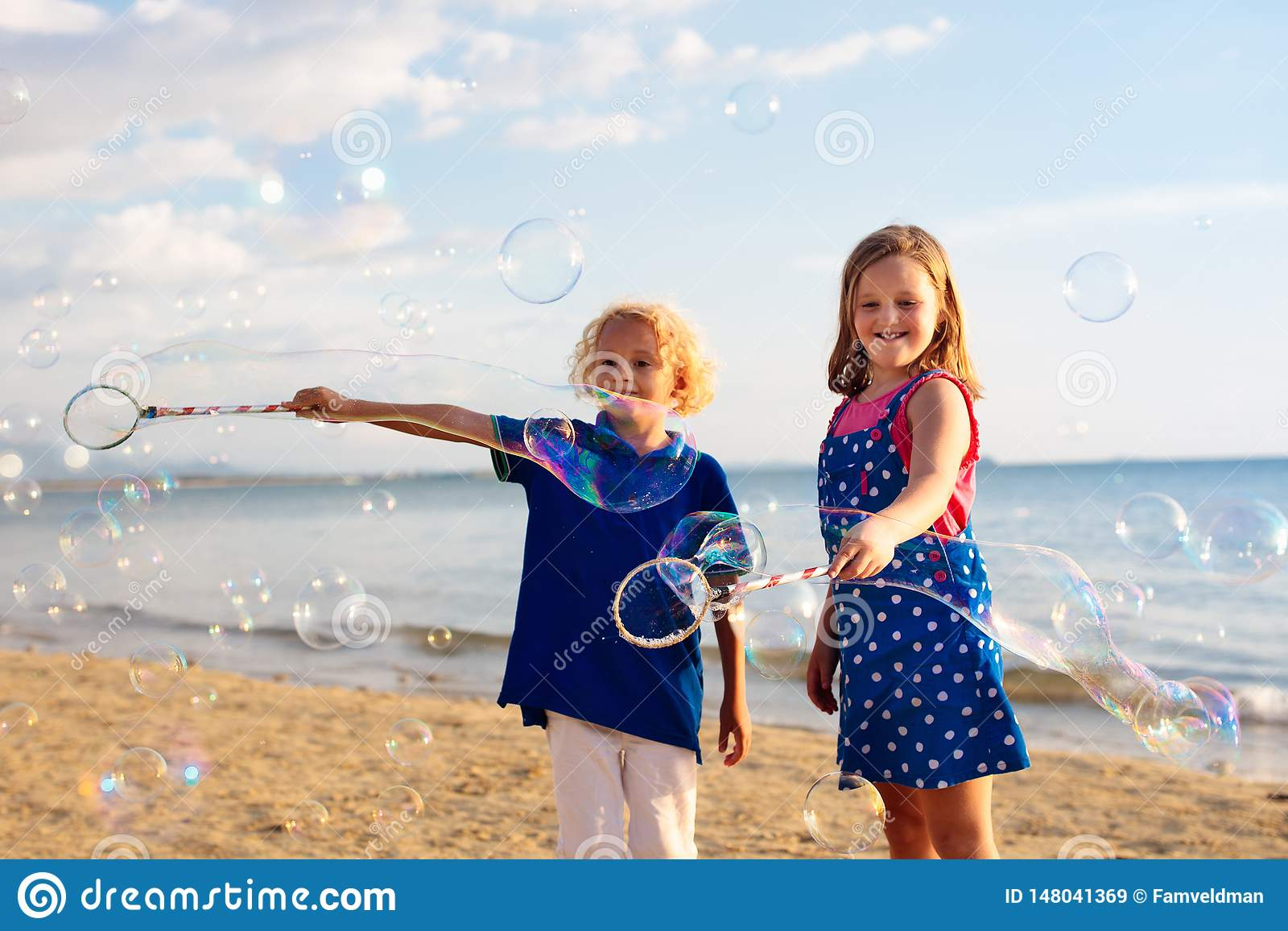 Ungar bl?ser bubblan p? stranden bubbles barnet