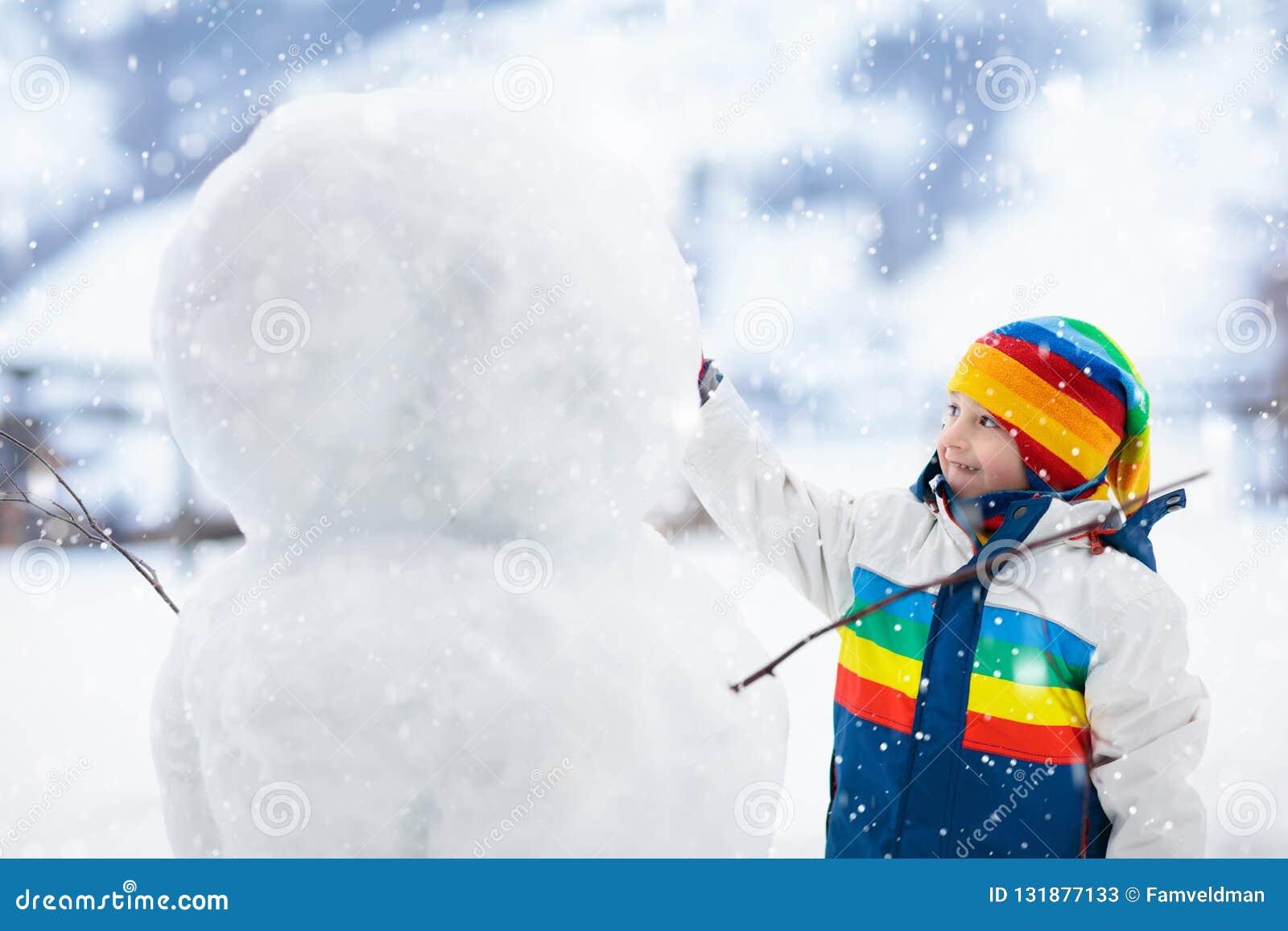 Ungar bygger snögubben Barn i snow körning av rolig pulkavinter
