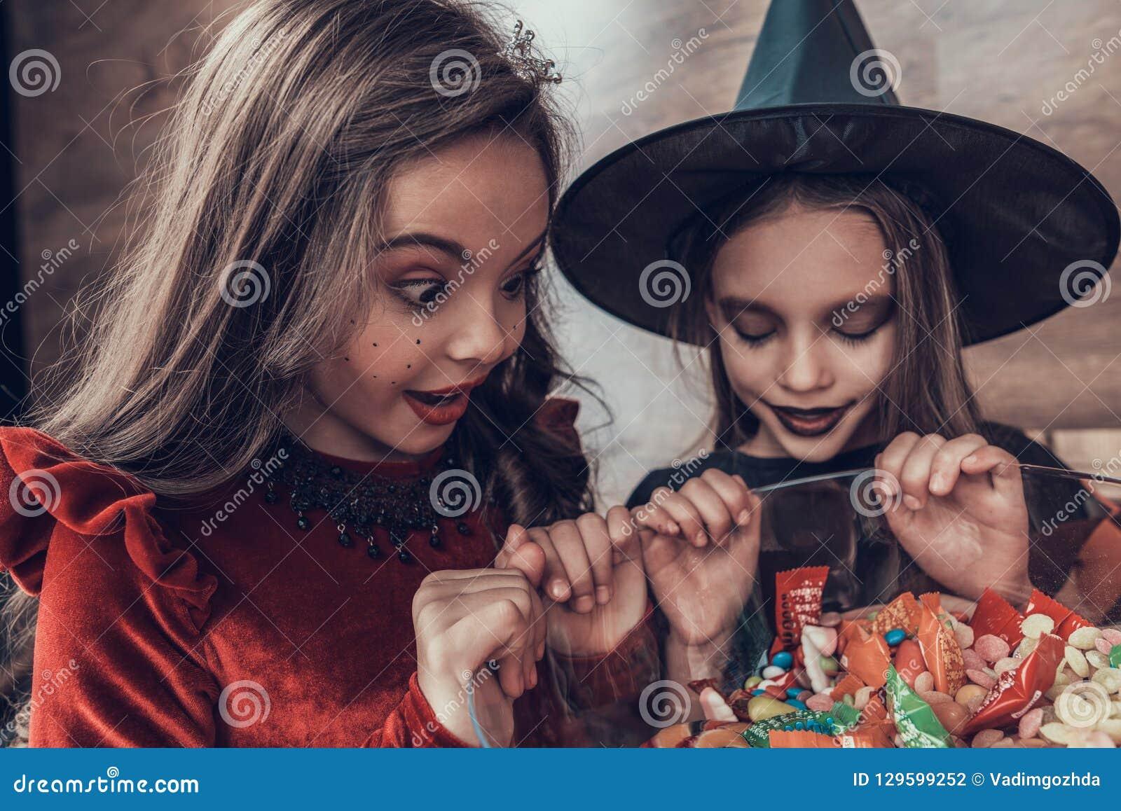 Ungar i dräkter som mycket ser in i bunken av Candys