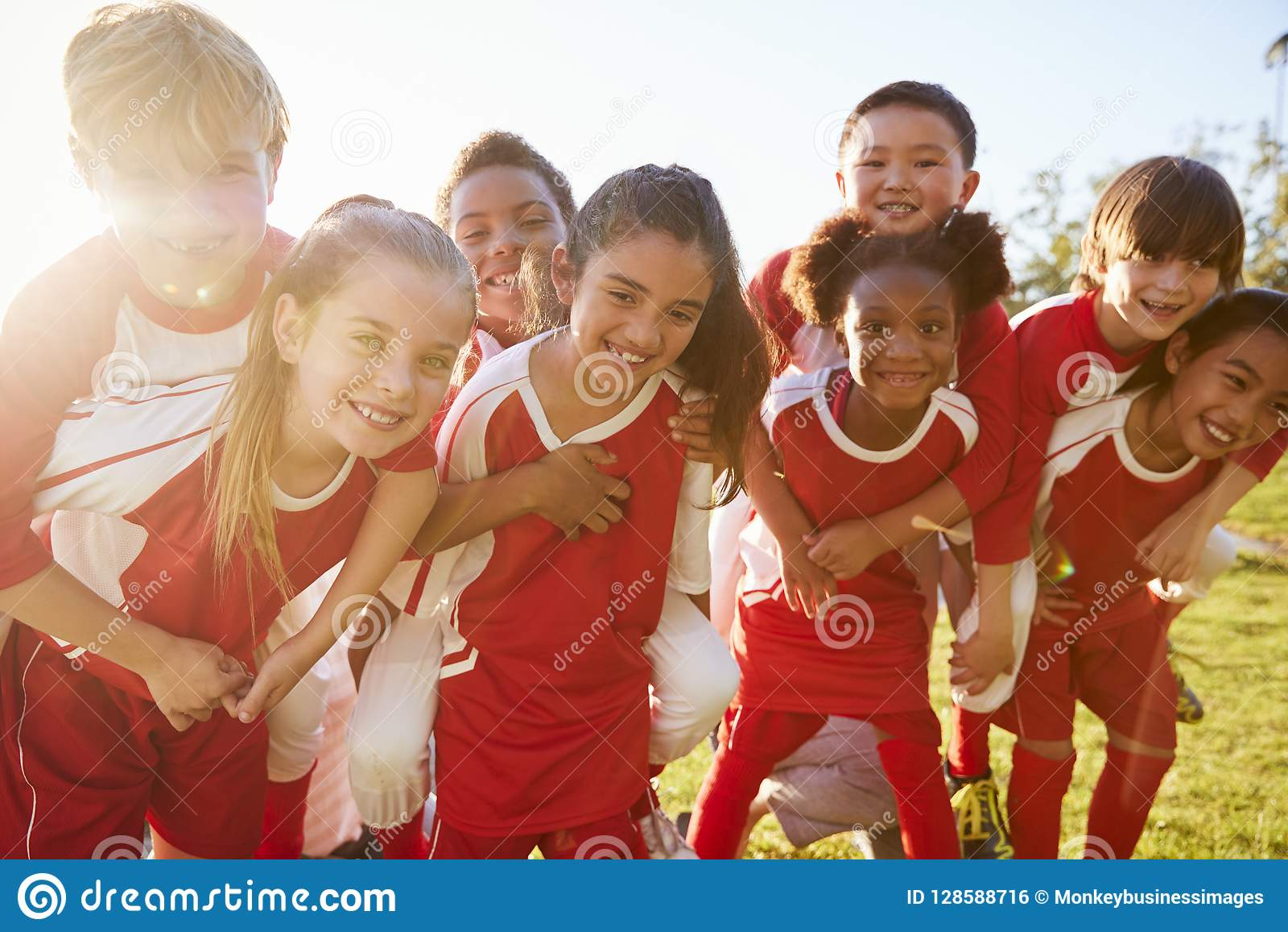 Ungar i grundskolasportlaget som utomhus piggybacking