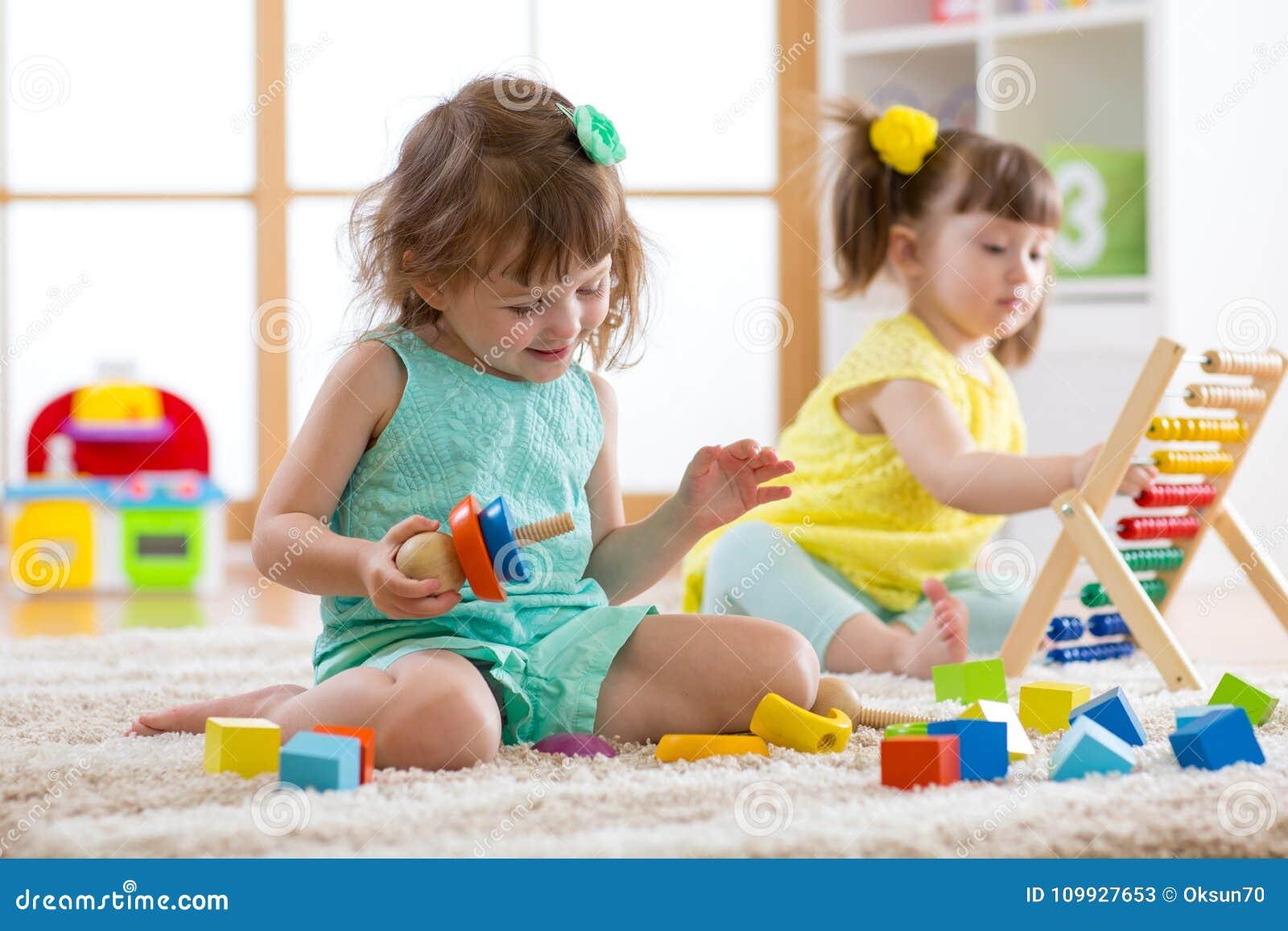 Ungar kopplar in i daycare Två litet barnbarn som spelar med bildande leksaker i dagis