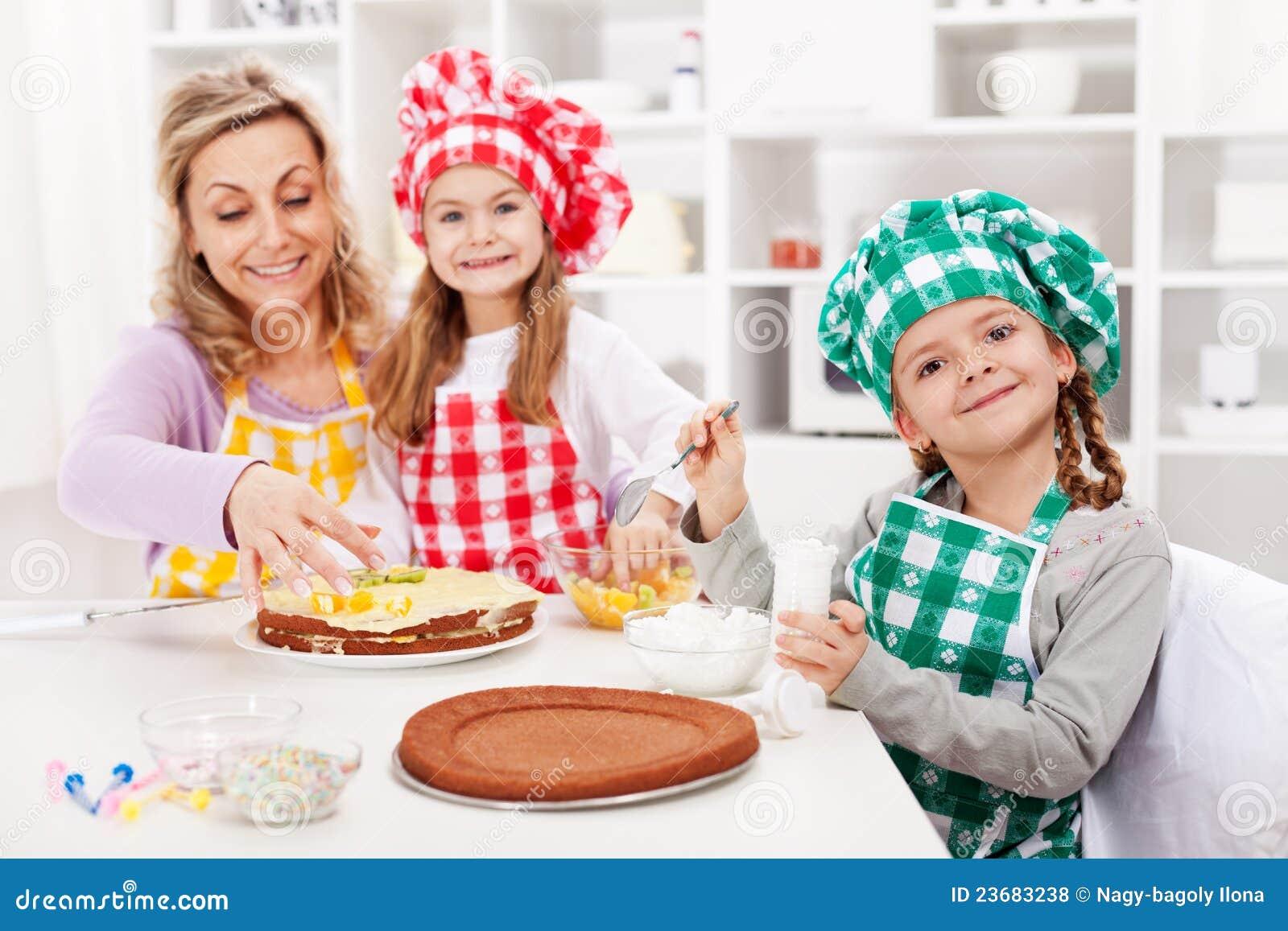 Ungar och deras moder som gör en cake