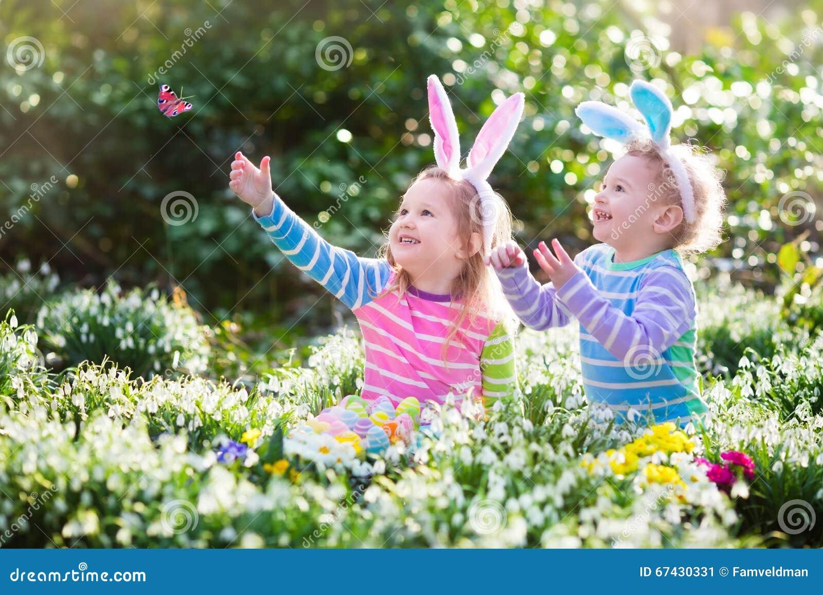 Ungar på jakt för påskägg i blommande vår arbeta i trädgården