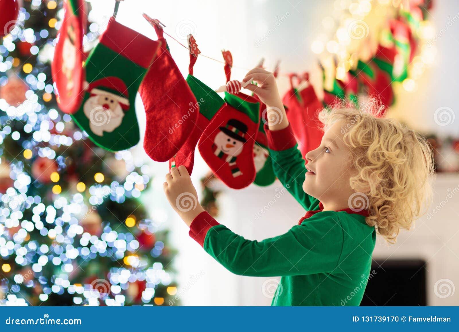 Ungar som öppnar julklappar Barn som söker för godis och gåvor i adventkalender på vintermorgon dekorerad jul