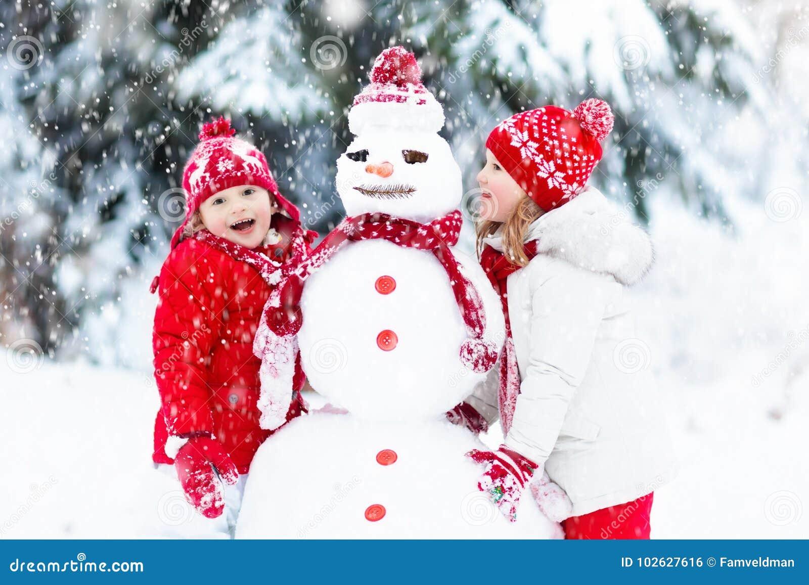 Ungar som bygger snowmanen Barn i snow körning av rolig pulkavinter