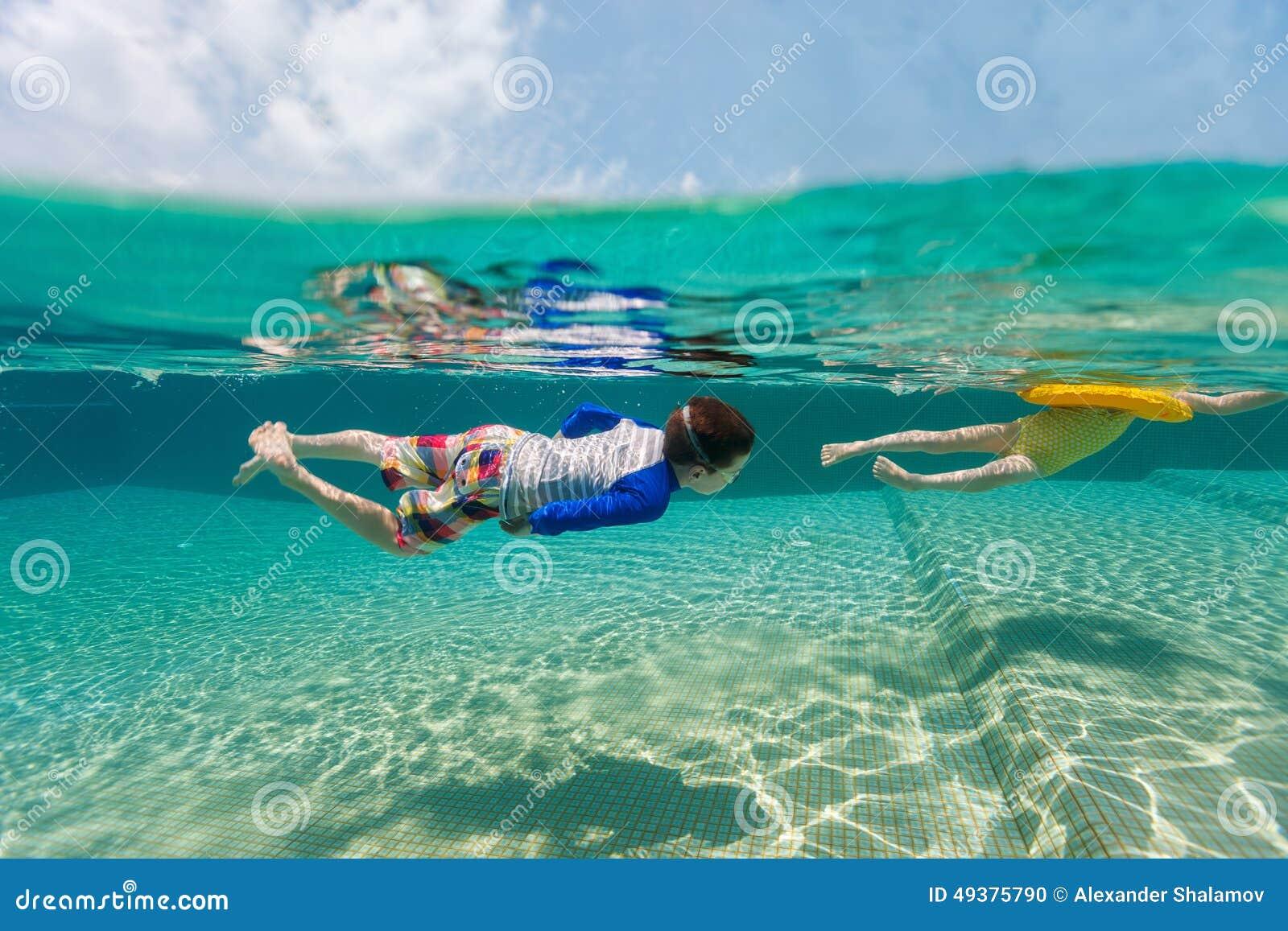 Ungar som har rolig simning på sommarsemester