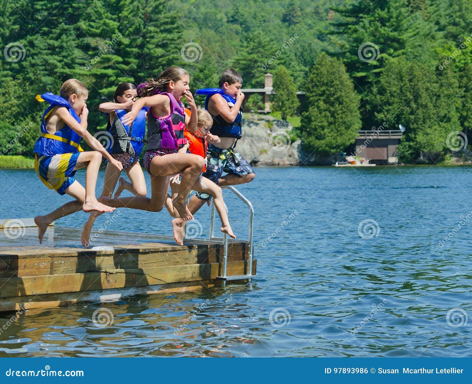 Ungar som har roligt hoppa för sommar av skeppsdocka in i sjön