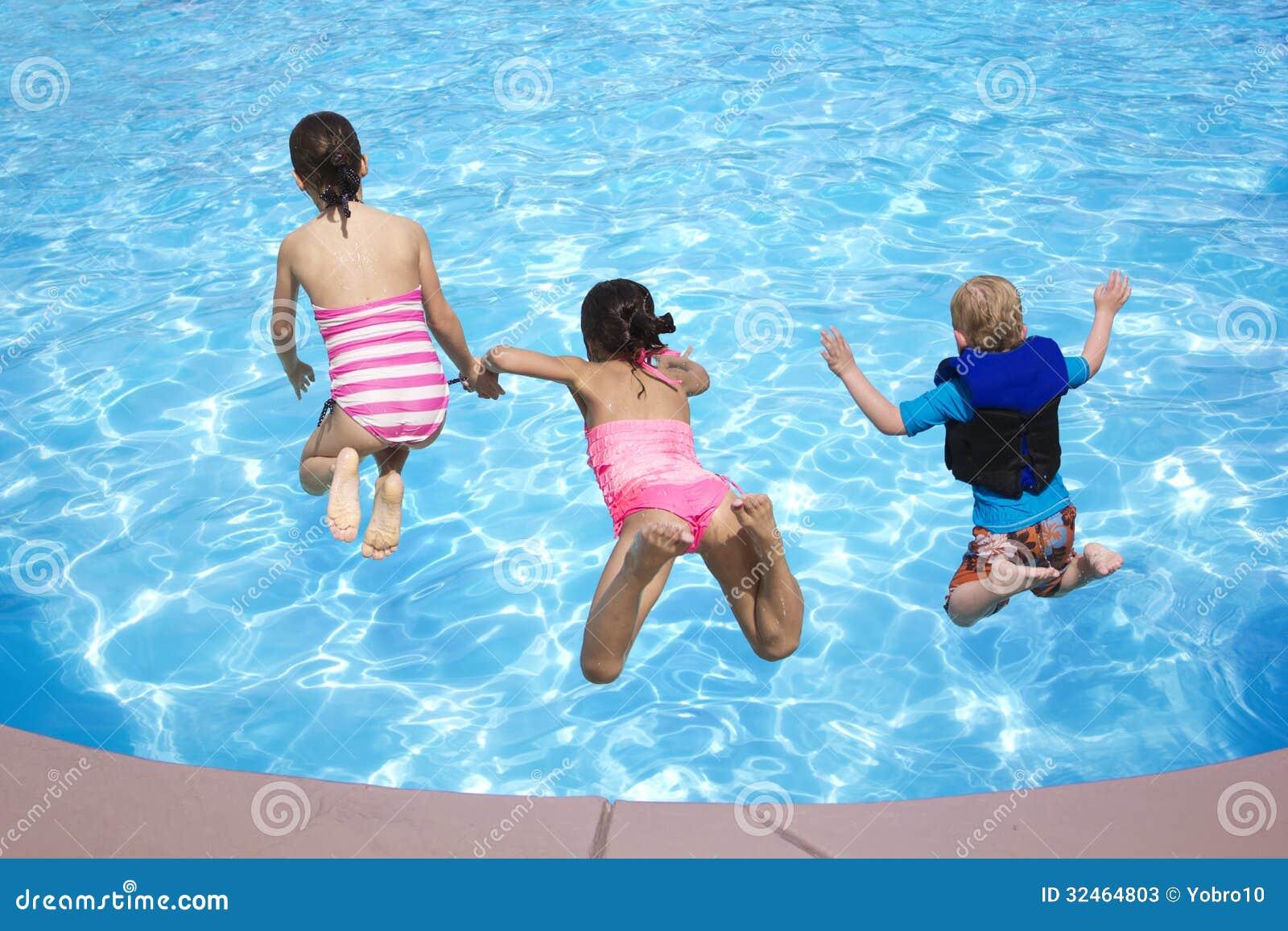 Ungar som hoppar in i simbassängen