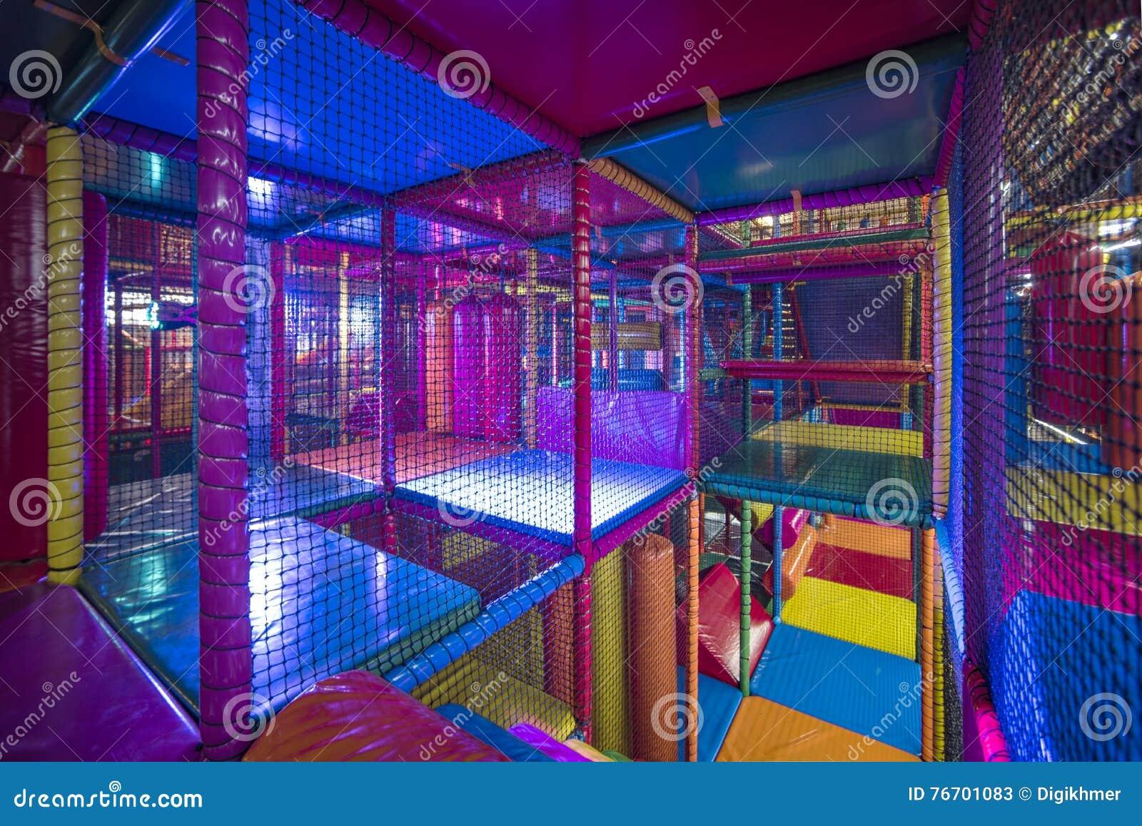 Ungar som kör inom en färgrik inomhus lekplats
