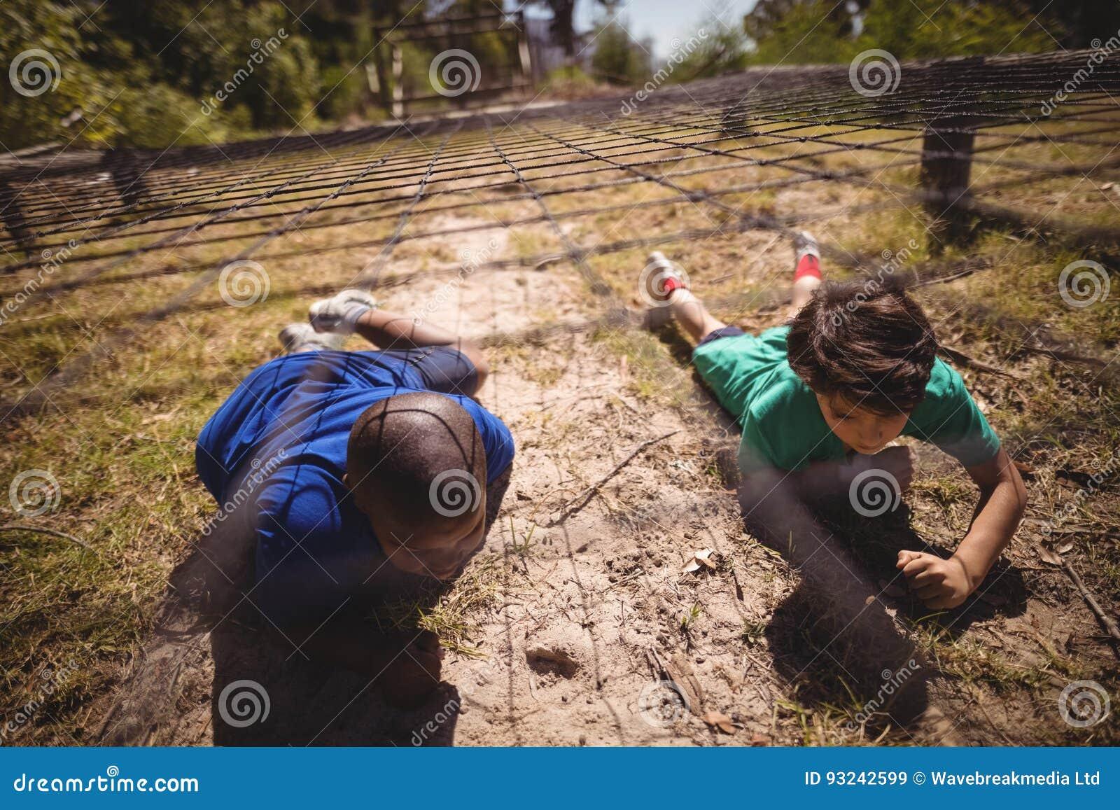 Ungar som kryper under det netto under hinderkurs