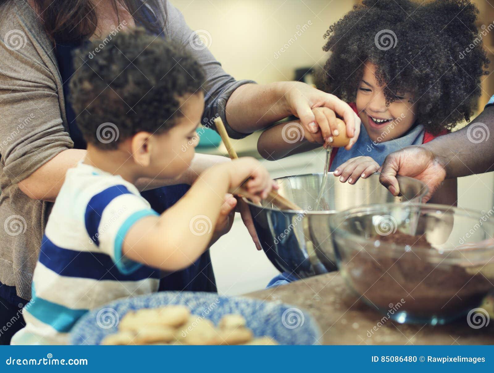 Ungar som lagar mat stekhett kakakökbegrepp