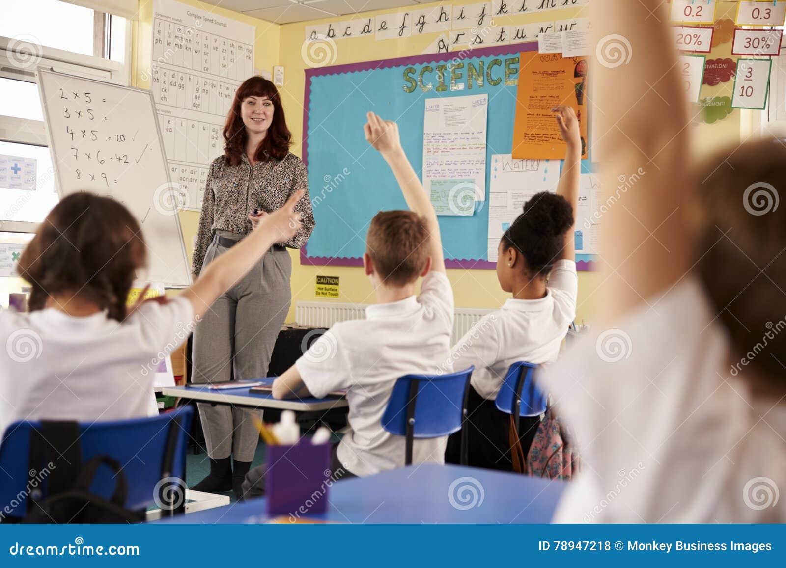 Ungar som lyfter händer i en grundskola för barn mellan 5 och 11 årgrupp, sikt för låg vinkel