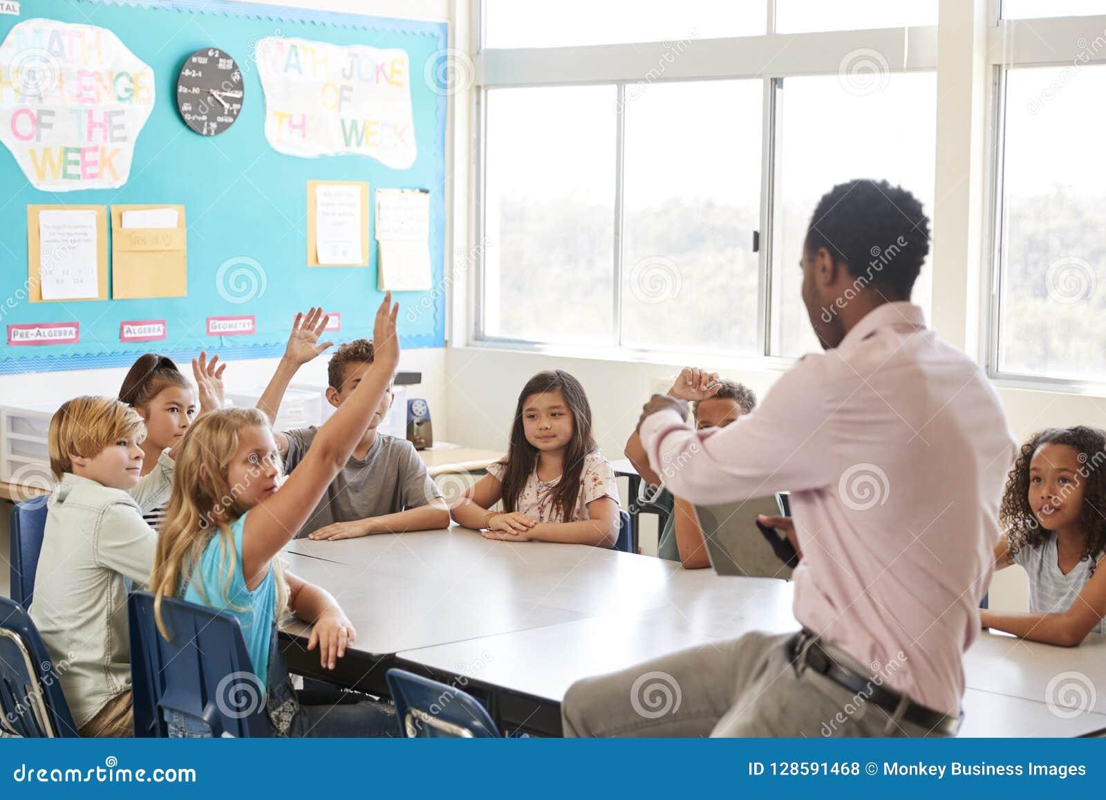 Ungar som lyfter händer till svaret i en grundskolakurs