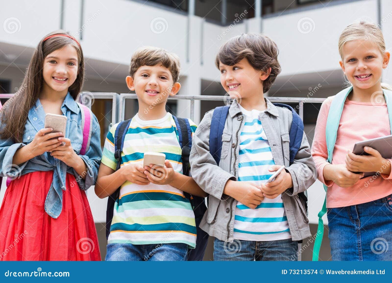 Ungar som rymmer mobiltelefonen och digitalt minnestavlaanseende på skola, terrasserar